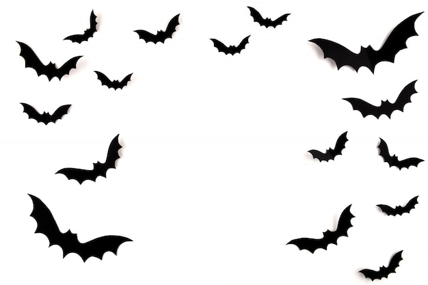ハロウィーンのペーパーアート。白地に黒い紙コウモリを飛んでください。