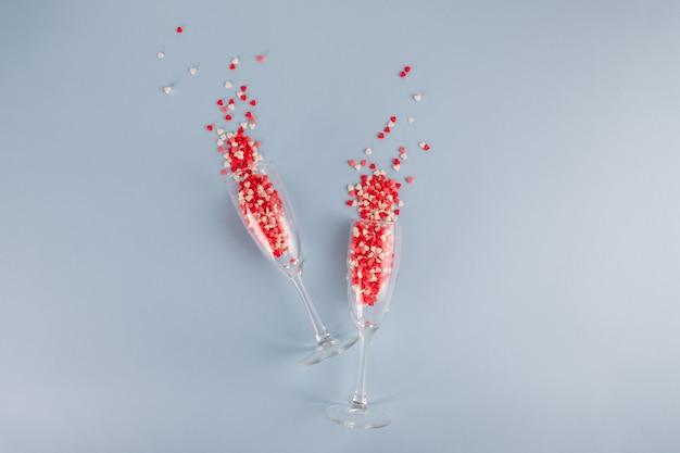 Два бокала для шампанского с всплеском красных сердечных конфет