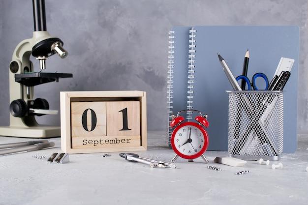 Группа школьных принадлежностей, красный будильник, микроскоп и деревянный календарь с датой