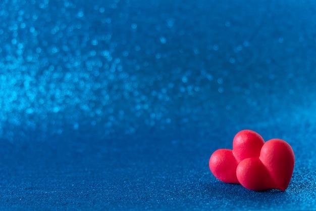 Ярко-красные сердца абстрактный синий фон боке. день святого валентина текстуры.