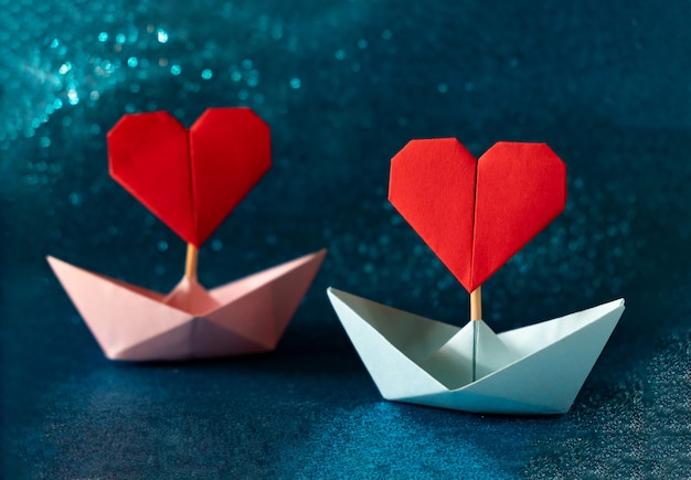 キラキラブルーの背景にピンクとブルーの紙の船。テキストのためのスペースを持つロマンチックなバレンタインデーのコンセプトです。