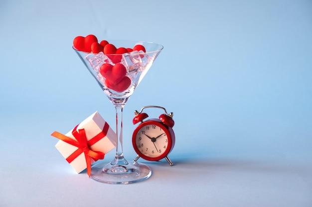 Стекло с красным сердцем в форме леденцов и льда. подарочная коробка и красный будильник на синем фоне. время для любви. день святого валентина, юбилей или свадебные торжества концепции. копировать пространство