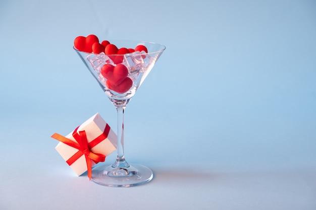 Стекло с красным сердцем сформировало леденец и лед и подарочную коробку сахара голубая предпосылка. время для любви. день святого валентина, юбилей или свадебные торжества концепции. копировать пространство