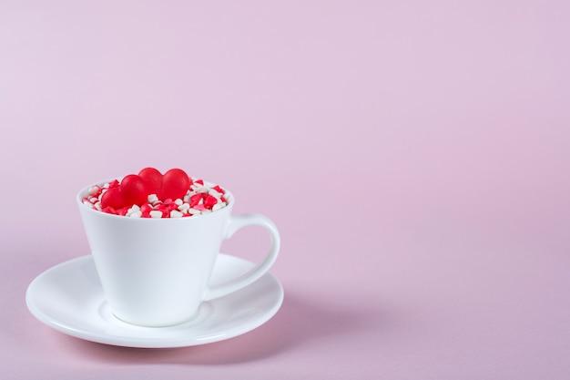 バレンタインデーの背景。多くの小さなカラフルなカップにハートを振りかけます。創造的なコンセプト。