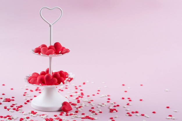 Белый двухуровневый поднос, полный многоцветной сладкой окропляет леденцы сердца. любовь и день святого валентина концепции.