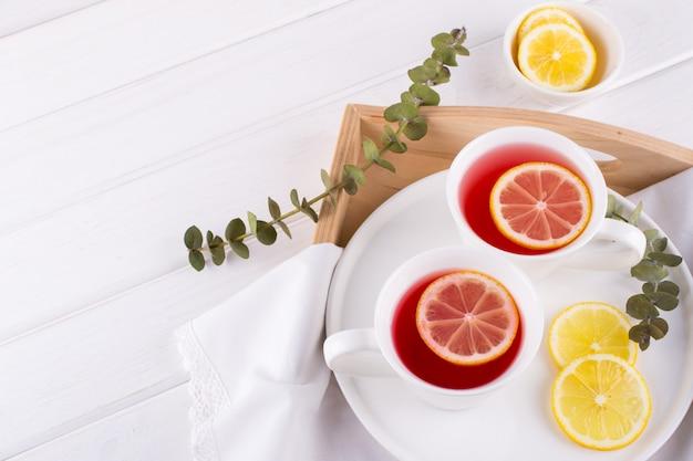 Две чашки красных фруктов и травяной чай с ломтиком лимона, вид сверху