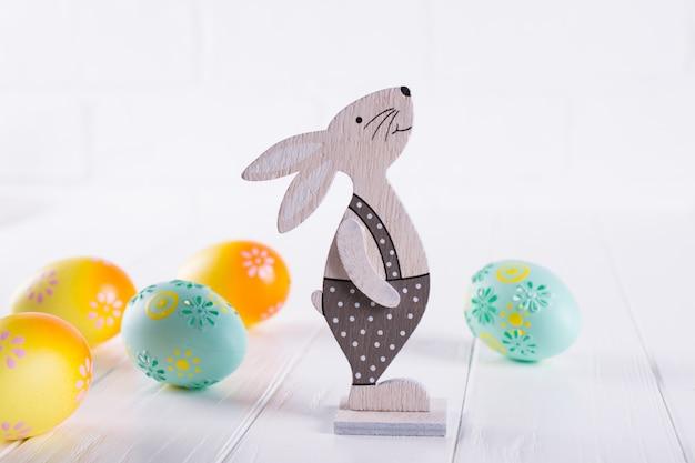 カラフルなイースターエッグ、装飾的な木製のウサギとイースターの組成物。レタリング用のテンプレート