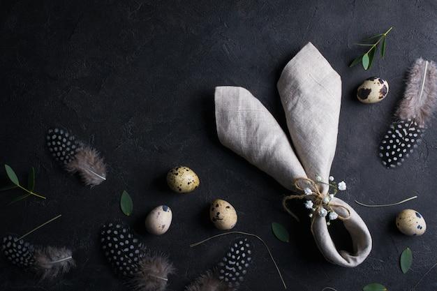 卵とイースター休日の背景。暗いさびた背景にウズラの卵、羽、ウサギの耳のリネンナプキンの平面図です。テキストのコピースペース