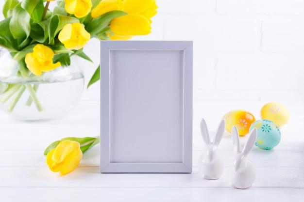 Макет рамы украшен желтыми цветами тюльпанов в вазе, кролика и яиц на белом фоне с чистым пространством для текста и дизайна