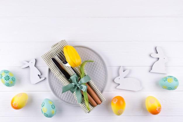 メニューの春のイースターの背景。イースターエッグの装飾、バニー、プレートにリネンのナプキン、白い木製のテーブルにキッチンカトラリー。フラットレイ