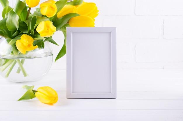 Макет рамы украшен желтыми цветами тюльпана в вазе на белом фоне с чистым пространством для текста и дизайна