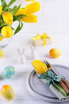 メニューの春のイースターの背景。イースターエッグの装飾、バニー、プレートにリネンのナプキン、白い木製のテーブルにキッチンカトラリー。