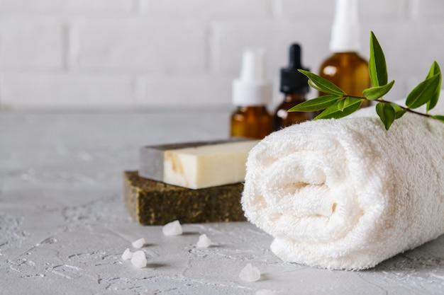 お風呂と自然化粧品のコンセプト。手作り石鹸と白いテーブルの上のタオル。スパとボディケア