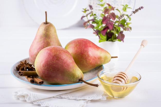 シナモンスティック、アニススターズ、白いキッチンテーブルの上の蜂蜜が付いている皿に新鮮な熟した有機甘い梨。
