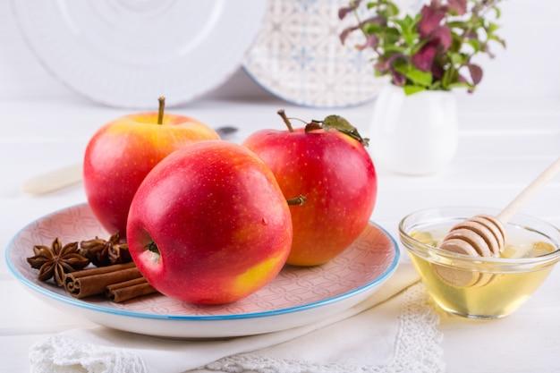 シナモンスティック、アニススター、白いキッチンテーブルの上の蜂蜜が付いている皿に新鮮で熟した有機甘いリンゴ。