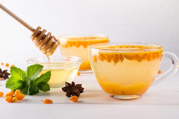 ガラスのカップでビタミン健康的な海クロウメモドキ茶、新鮮な生海クロウメモドキの果実とシナモンスティック、アニススター、ミント、白いキッチンテーブルの上の蜂蜜。