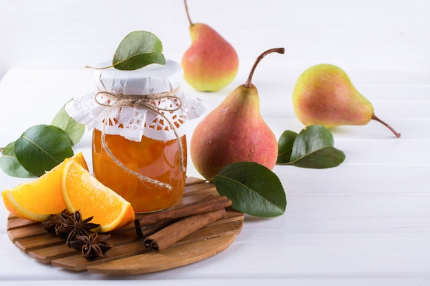 熟した洋ナシ、シナモンスティック、アニススター、テーブルの上の緑の葉が入ったガラスの瓶の中の洋ナシとオレンジのジャム。