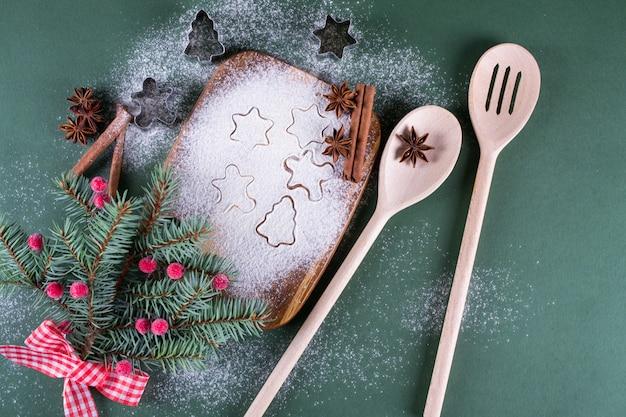 クリスマスのベーキング。まな板の上の装飾、小麦粉、スパイス、クッキー型とモミの木。