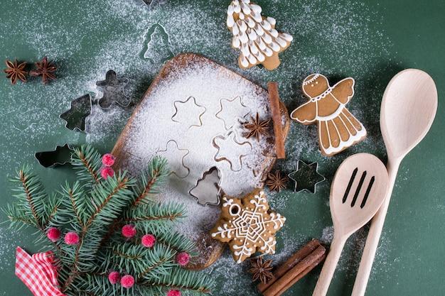 クリスマスのベーキング。まな板の上の装飾、小麦粉、スパイス、クッキー型とモミの木。緑の表面に装飾が施された美しいクッキー
