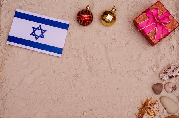 イスラエルの新年とクリスマス休暇。海とビーチでの休暇、トリートメント。ギフトの背景が付いている砂の上のイスラエル共和国の旗