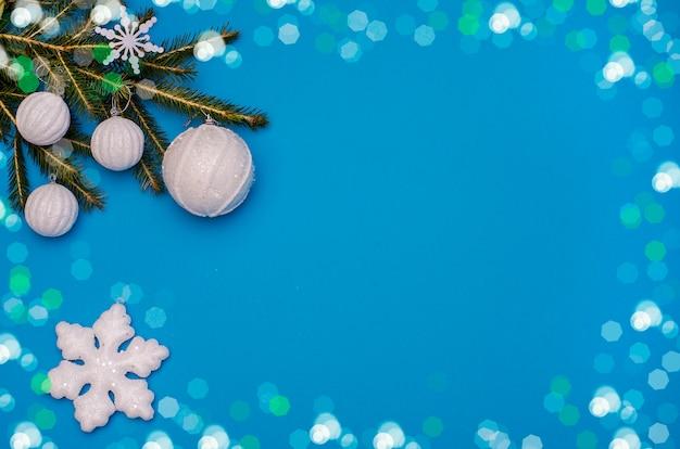 Открытка на новый год и рождество на синем фоне с ветвями елки и белыми шарами с боке кадра и снежинки. китайский новый год.