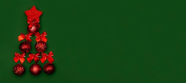 Открытка баннер на рождество и новый год на зеленом фоне с минималистичной елки из красных новогодних шаров и красных бантов. китайский новый год.