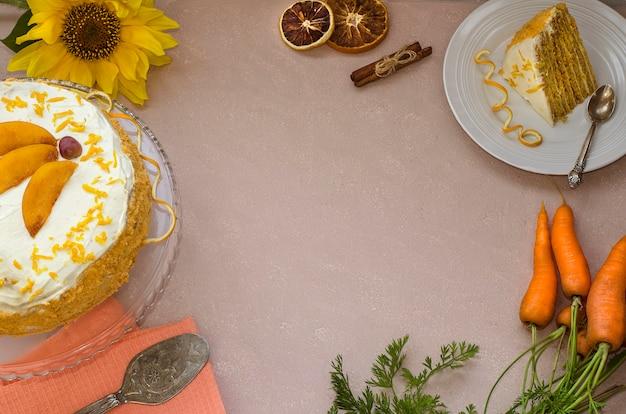 Морковный торт. многослойный морковный торт на бежевом фоне с копией пространства украшен апельсиновой цедрой с желтым цветком и морковью. вид сверху. домашние пирожные