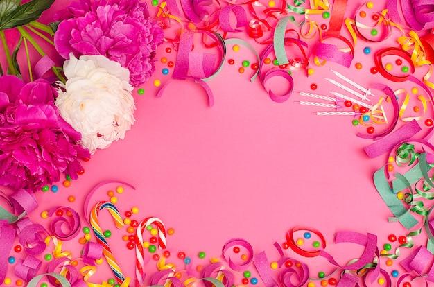 Праздничный фон. розовые и белые пионы на розовом фоне с рамкой из конфет и мишуры.