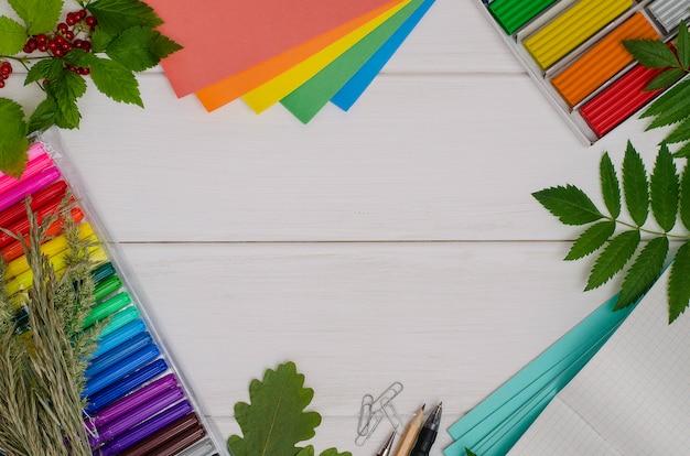 Снова в школу: состав школьных принадлежностей с копией пространства на белом фоне деревянные