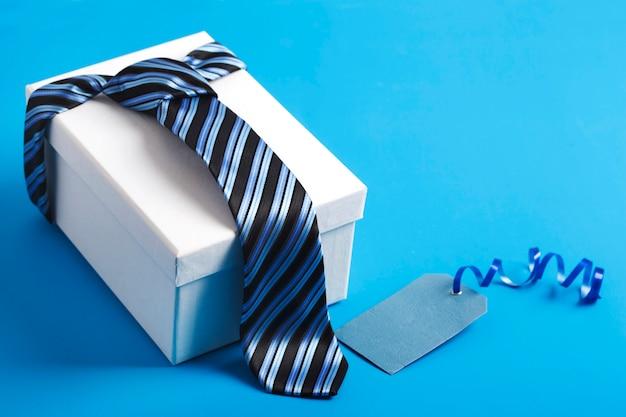 Подарочная коробка с синим полосатым галстуком. счастливая идея дня отца, знак, символ. праздничный фон