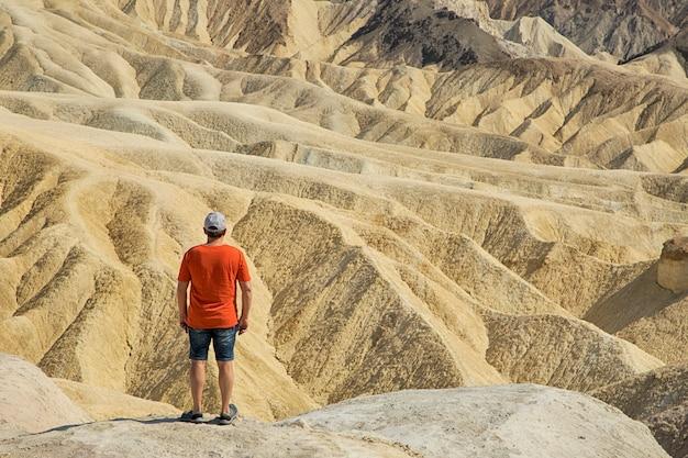 男は砂漠のハイキングで一人で立っています。ザブリスキーポイント。カリフォルニア州デスバレー