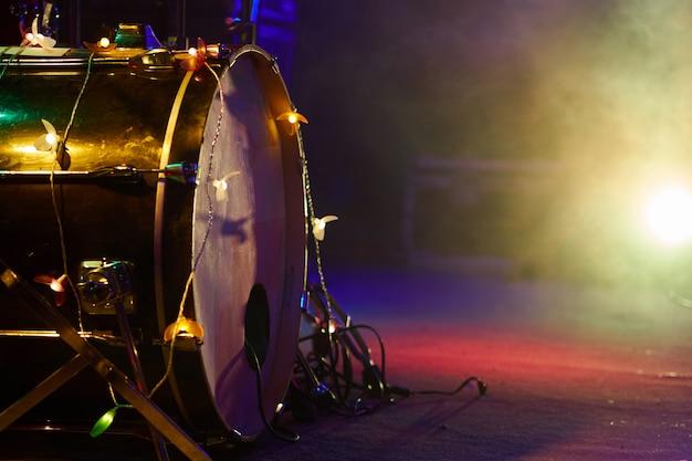 Барабанная установка на сцене басового барабана крупным планом в тумане и разноцветном освещении