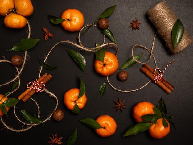 Апельсины с веревкой и корицей и зелеными листьями на черном фоне. натюрморт с плоской планировкой