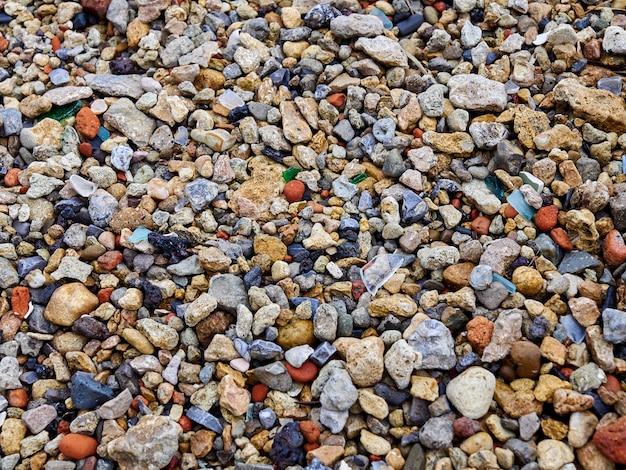 色の岩の小石のビーチをクローズアップテクスチャ背景