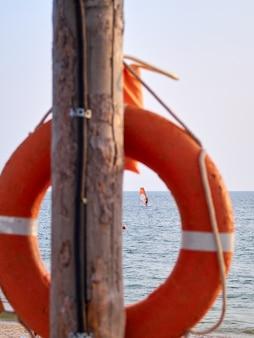 Оранжевый спасательный круг висит на деревянной колонне на песчаном морском пляже