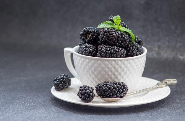 テーブルの上のブラックベリーと白いカップ