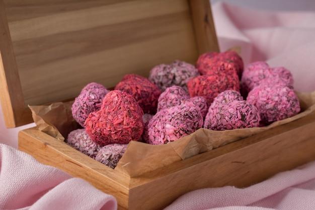 Энергетические укусы в форме сердца на день святого валентина в деревянной коробке на розовой ткани, крупным планом
