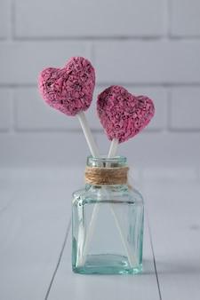 ハート形の白い木製のテーブルの上のボトルにバレンタインデーのエネルギー刺され