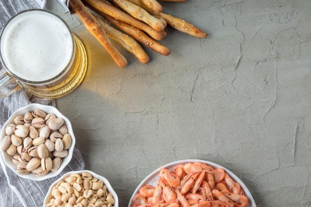 Плоская композиция с золотым пивом и вкусными закусками на сером столе