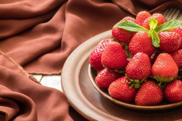 テーブル、テキスト用のスペースに新鮮な赤いイチゴのプレート