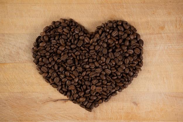 木製の背景にコーヒー豆で作られた心