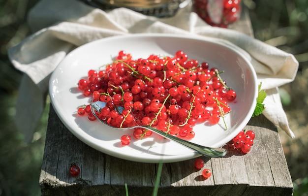 Красная смородина на белой плите на деревянной доске в саде на солнце.