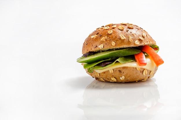 チーズと野菜の背景を持つ健康的なベジタリアンハンバーガー