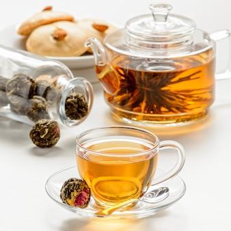 Экзотический зеленый чай с цветами в стеклянном чайнике и чашка на белом