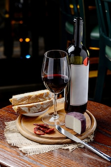 天日干しトマトと木の上のチーズと赤ワインのボトル