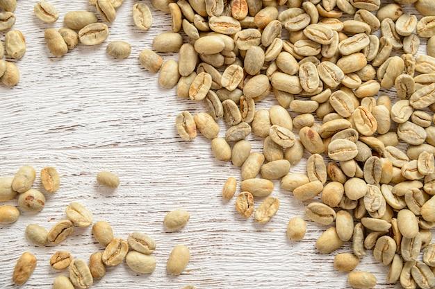 Зеленый кофе в зернах на деревянном столе текстуры