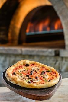 テーブルの上のピザと背後にある本物の火