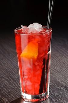 Свежий экзотический коктейль с кубиками льда и апельсином на деревянном столе