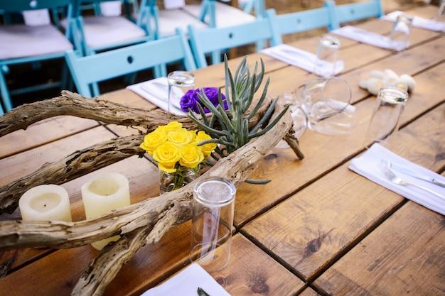 素朴な結婚式の装飾、キャンドルと花の結婚式のテーブルセッティング。