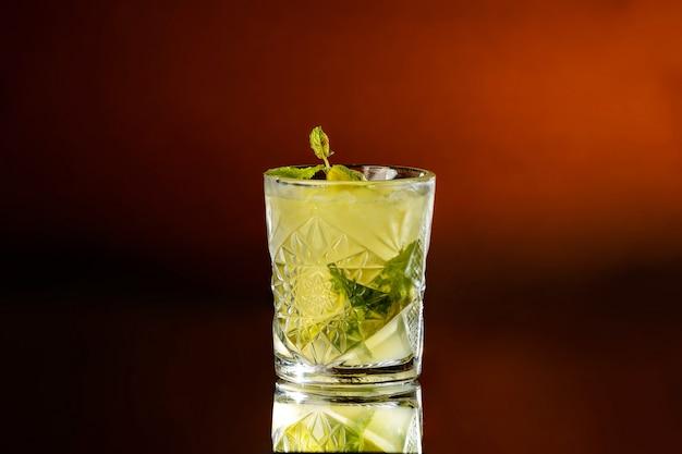 オレンジブラウンの背景にサワーライム、ラム酒、ミント、アイスキューブからアルコールモヒートでいっぱいのガラス。